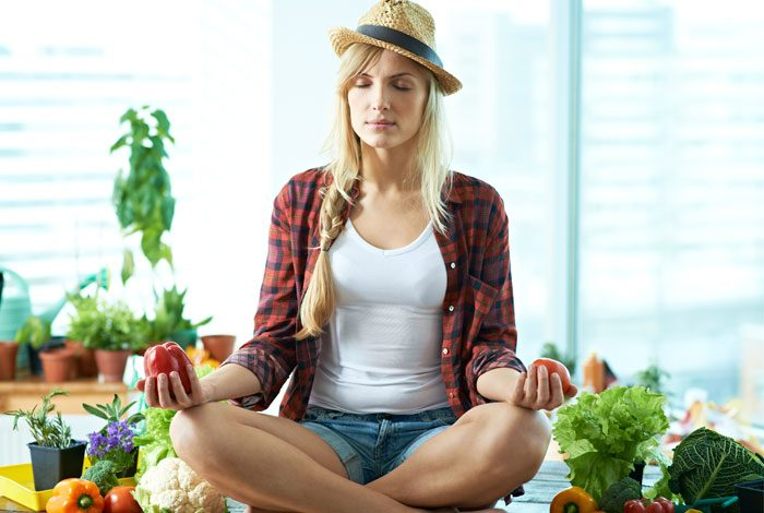 Woman doing yoga with vegetables